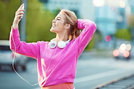 Attractive and sporty girl exercising on the bridge. Living healthy lifestyle. Relaxing with cellphone after jogging. Stock Photo