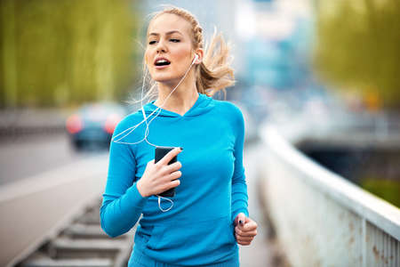 Young blonde woman jogging and listening music. Stock Photo