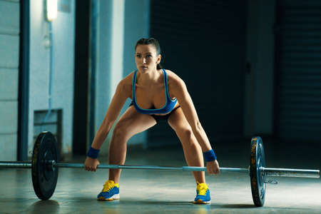 Young attractive fit woman pulling up weight.