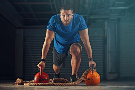 Jonge atleet man training met kettlebell in garage.