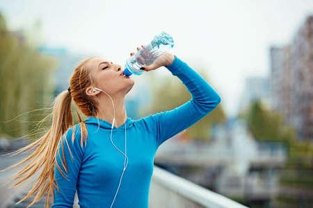 Jonge blonde vrouw is vroeg in de ochtend joggen.