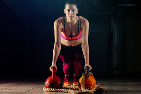 Young athlete woman exercising with kettlebell in garage.