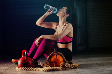 Young athlete woman drinking water after exercising with kettlebell in garage.