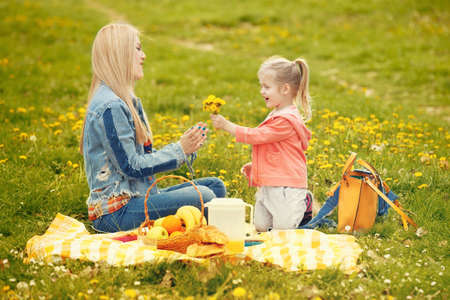Portrait of happy family of two people. Blonde mum and daughter enjoying picnic in park.