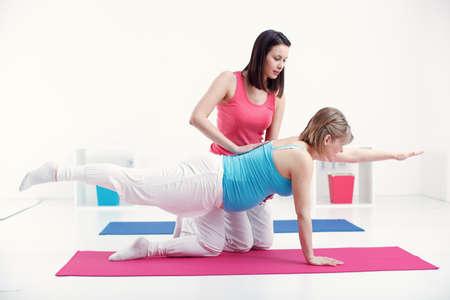妊娠中の女性は彼女のトレーナーと運動し、彼女の体の世話をします。 写真素材