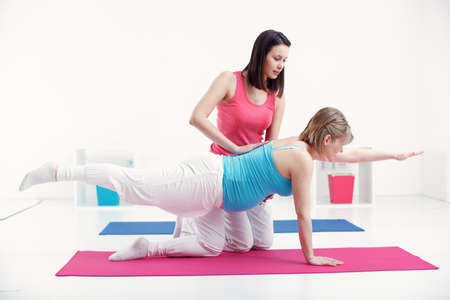 Pregnant woman exercise with her trainer and take care of her body.