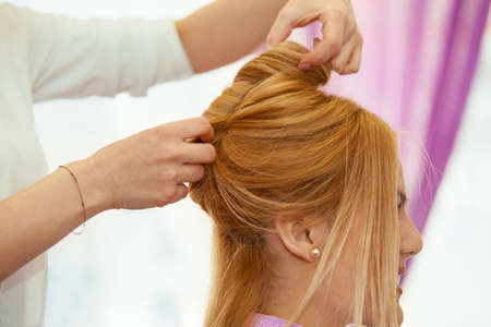 Young beautiful blonde woman enjoying hair treatment.