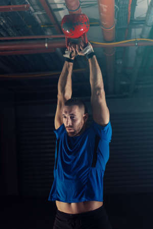 Young athlete man is exercising with kettlebell in garage. Stock Photo