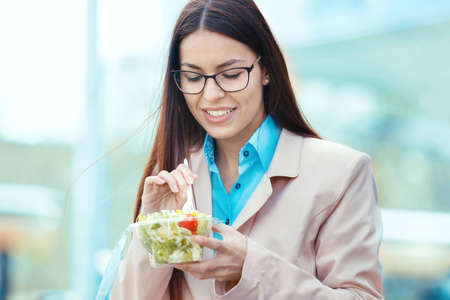 Young businesswoman eating salad on lunch break.