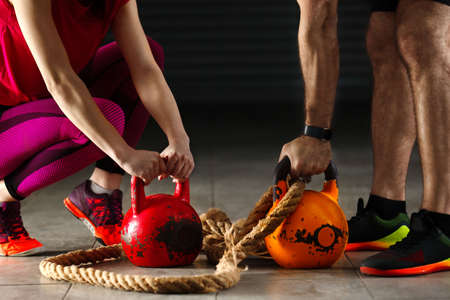 Young athlete couple exercising with kettlebell in garage. Stock Photo
