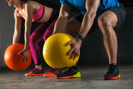 Young athletecouple exercising with ball in garage.
