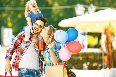 Happy family walking along the street with shopping bags. Stock Photo