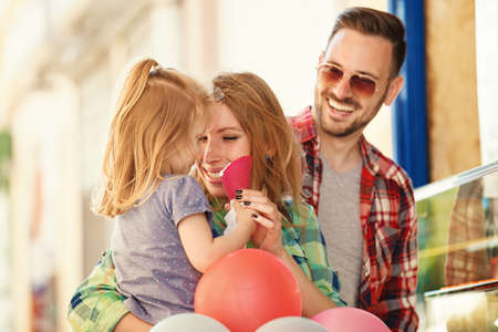 Happy family enjoying ice-cream in cafe after shopping. Stock Photo