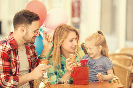 Happy family enjoying ice-cream in cafe after shopping. Stok Fotoğraf