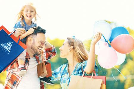 幸せな家族が買い物袋が付いている通りを歩いています。 写真素材