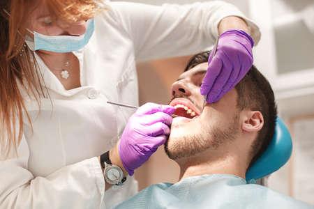 여성 치과 의사와 젊은 남자 치과 사무실에서 환자입니다. 스톡 콘텐츠