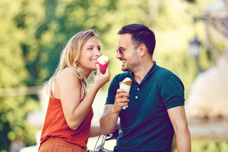 Portrait of happy young couple eating ice-cream in the city.