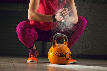 Young athlete woman is having training with kettlebell in garage. Stock Photo