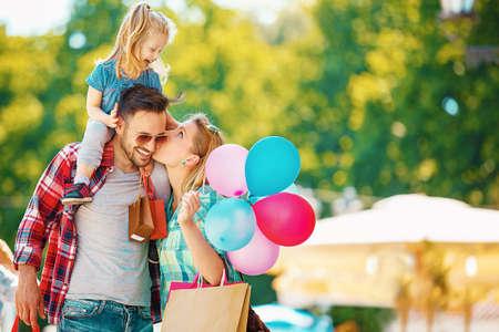 Glückliche Familie zu Fuß entlang der Straße mit Einkaufstüten.