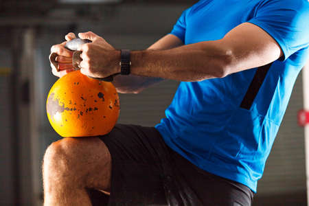 Young athlete man is training with kettlebell in garage.