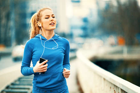 Young blonde woman is jogging on the bridge early in the morning. Imagens