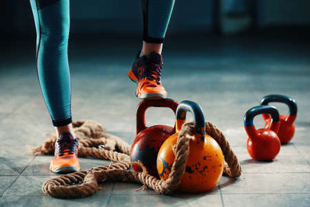 Young athlete woman is having training with kettlebell in garage. Stok Fotoğraf