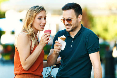 Portrait of happy young couple riding a bike in the city and eating ice-cream.