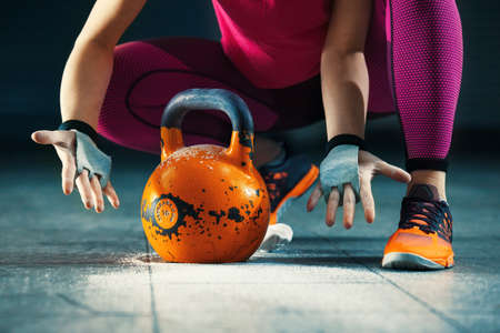 Young athlete woman is having training with kettlebell in garage. 版權商用圖片
