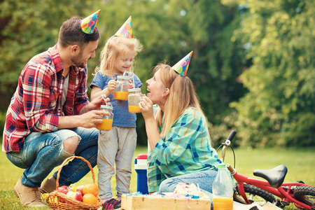 children party: Happy family of three celebrating birthaday party in the park. Stock Photo