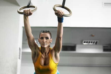 Young fit woman pulling up on gymnastic rings. Stock Photo