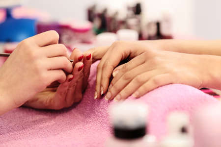 Woman hands receiving manicure and nail care procedure. Close up concept. Manicurist pushing cuticles on females nails.