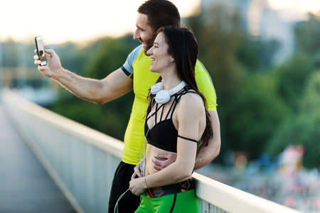 Early morning workout. Happy couple relaxing with cellphone after exercising on the bridge. Living healthy lifestyle