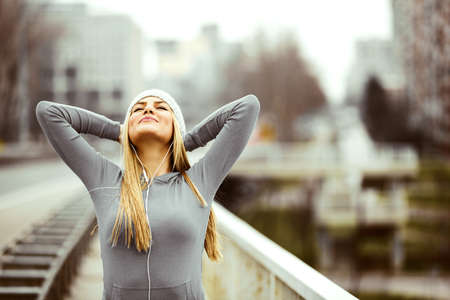 Young blonde woman is training on the bridge early in the morning.