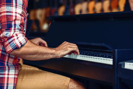 若い男は、楽器店でピアノを弾きます。 写真素材