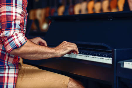 Young man is playing piano in musical instrument store.