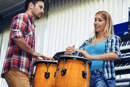 Musicians playing congas in musical instrument store.