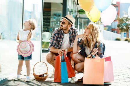 Gelukkige familie met boodschappentassen en ballons die op straat lopen.