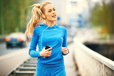 Young blonde woman is jogging on the bridge early in the morning. Stok Fotoğraf