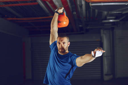 Young athlete man is training with kettlebell.