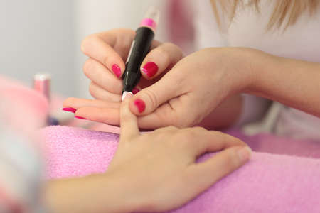 Woman hands receiving manicure and nail care procedure. Close up concept. Manicurist removing nail polish on females nails.