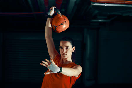 Young athlete woman is training with kettlebell.