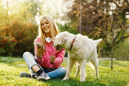 若いブロンドの女性は彼女のレトリーバーと公園でリラックスです。