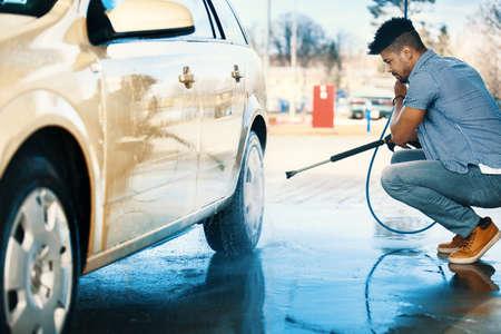 若いハンサムな男は、屋外の車を洗っています。 写真素材