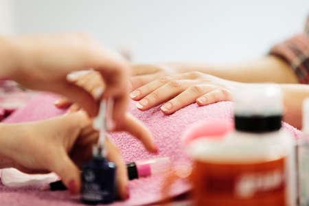 受信の女性の手はマニキュアし、爪のケア手順。コンセプトを閉じます。