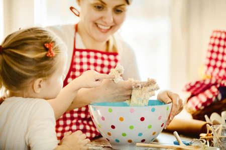 Junge Mutter und ihre schöne 4 Jahre alte Tochter machen Teig für Kekse. Lebensstil Foto. Standard-Bild - 84632732