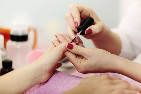Woman hands receiving manicure and nail care procedure. Close up concept. Stock Photo