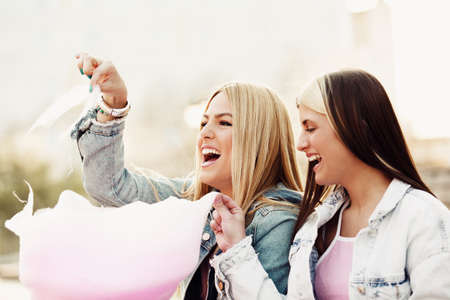 Happy young women having fun in the city and eating cotton candy.