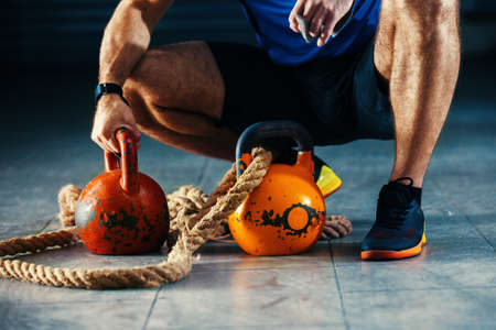 Young athlete man is having training with kettlebell in garage.