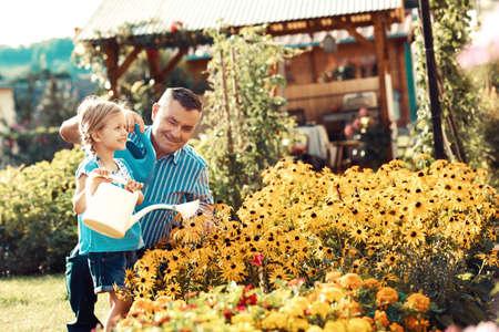 祖父は孫娘の花に水をまきます。