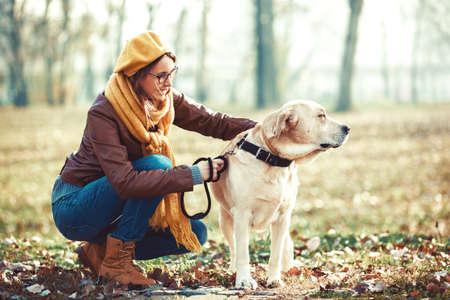 젊은 여자가 그녀의 래브라도 가을 즐기기.